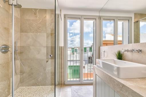 La ventana grande ofrece luz natural al baño