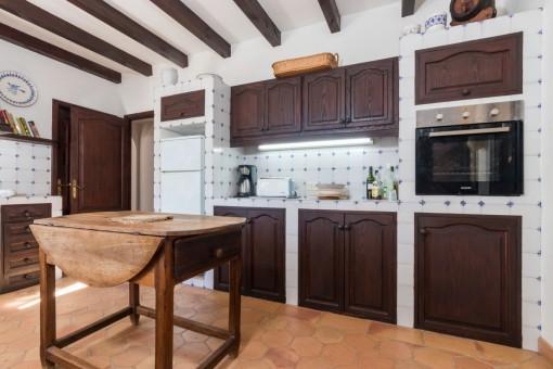La cocina tiene armarios de madera y baldosas