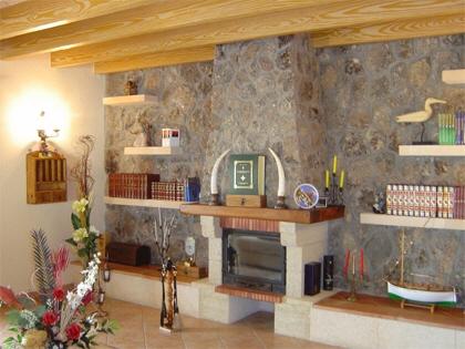 Vista parcial del Salón con chimenea, pared forrada de piedra y vigas de madera vista.