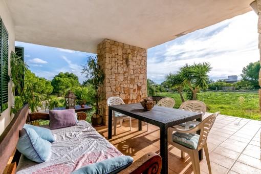 Bonita zona de asientos en la terraza cubierta con vistas al jardín