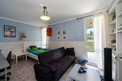 Dormitorio con escritorio y acceso al balcón