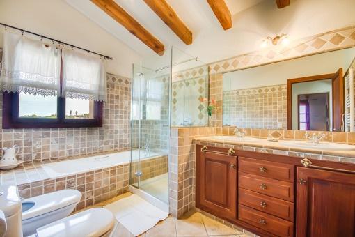Baño inundado de luz con bañera y ducha