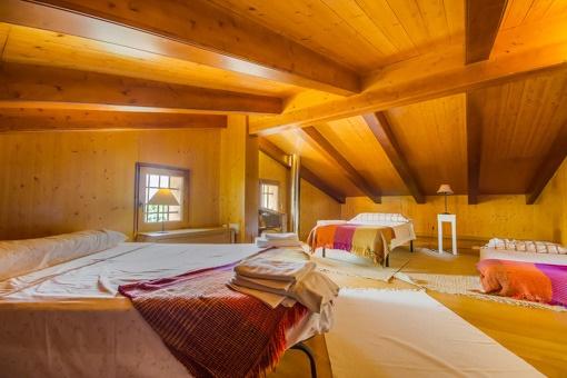 Dormitorio con tres camas en el ático