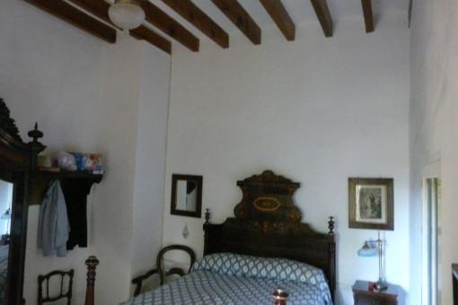 Dormitorio con techo con vigas vistas