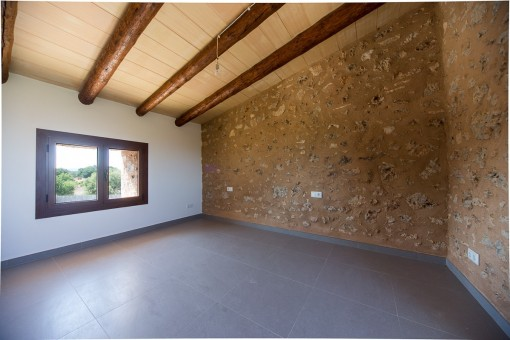 Dormitorio con pared de piedras natural