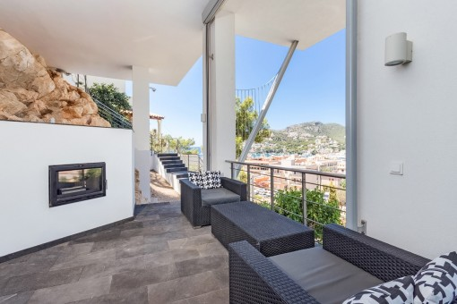 Zona de estar en la terraza cubierta con chimenea
