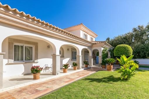 Entrada con terraza cubierta y jardín bonito
