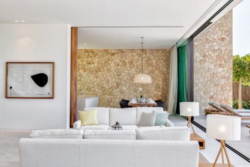 Hermoso salón-comedor con pared de piedra natural