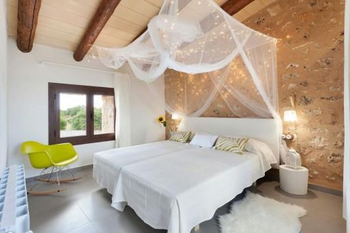 Acogedor dormitorio con pared de piedra natural