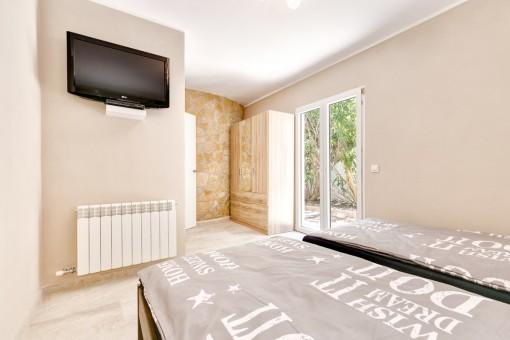 Dormitorio con pared de piedra natural