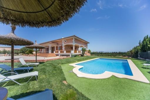 Zona de piscina preciosa con camas solares para disfrutar en el sol