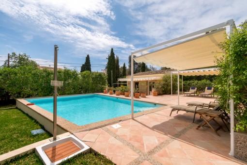 Jardín grande con piscina y tumbonas