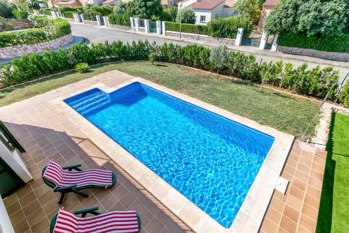 Jardín soleado con piscina