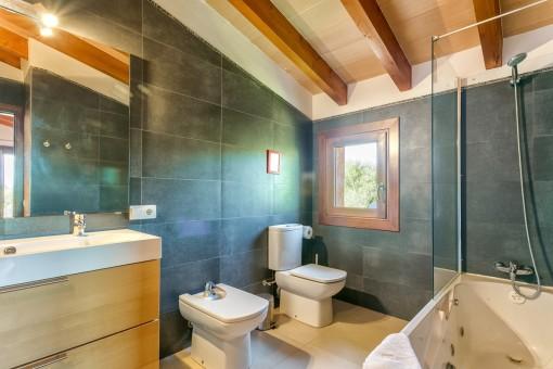 Baño en suite con bañera y luz natural