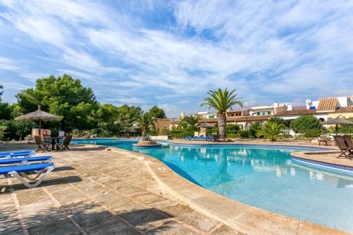 Gran piscina comunitaria que ofrece varias opciones para relajarse