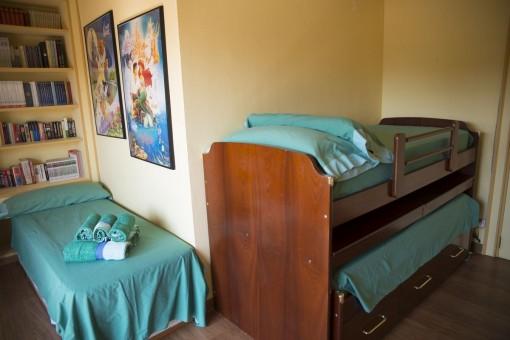 Dormitorio de huéspedes con cama alta práctica
