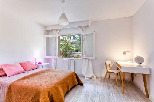 Dormitorio inundado de luz con una cama doble