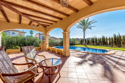 Zona de estar en la terraza cubierta con vistas a la piscina y al jardín