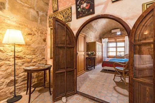 Una puerta de madera lleva desde el salón al dormitorio
