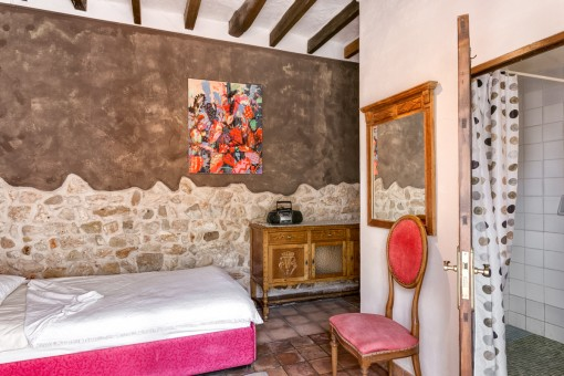 Dormitorio con pared de piedra vista original