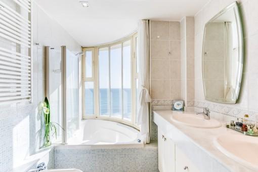 Luminoso baño con bañera y vistas al mar
