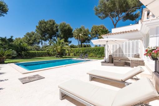 Maravillosa área exterior con piscina, césped verde y terraza soelada