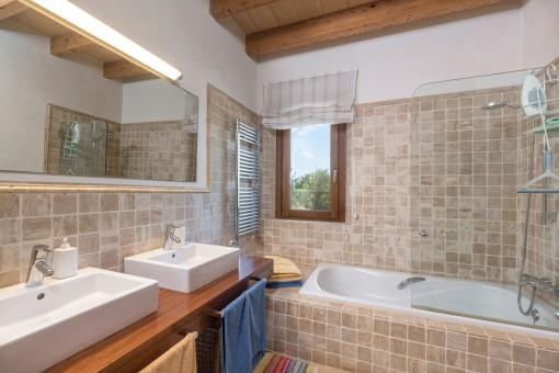 Baño encantador con lavabo doble y bañera