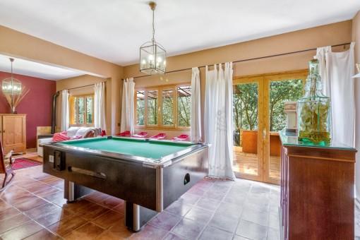 Área de estar con mesa de billar y acceso a la terraza
