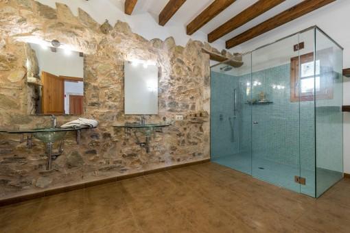 Único baño con fachada de piedra y ducha con mampara de vidrio