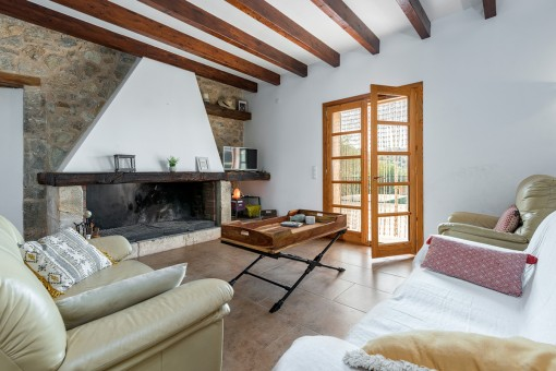 Cómoda área de estar con acceso a la terraza y chimenea con fachada de piedra