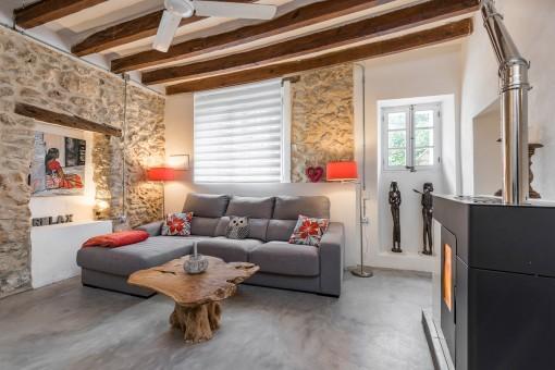 El área de estar tiene muros de piedra y vigas de madera