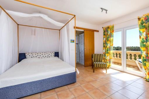 Dormitorio con baño en suite y balcón