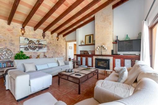 Área de estar con pared de piedra y chimenea