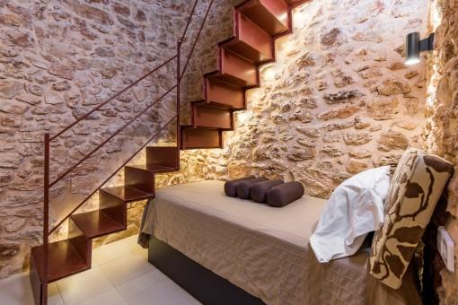 Dormitorio con auténtica pared de piedra