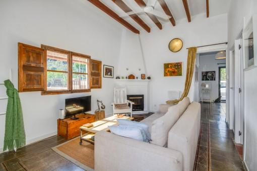 Área de estar con chimenea y vigas de madera