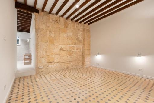 Dormitorio principal con pared de piedra arenisca
