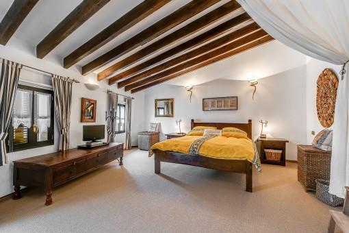 Dormitorio con techo alto