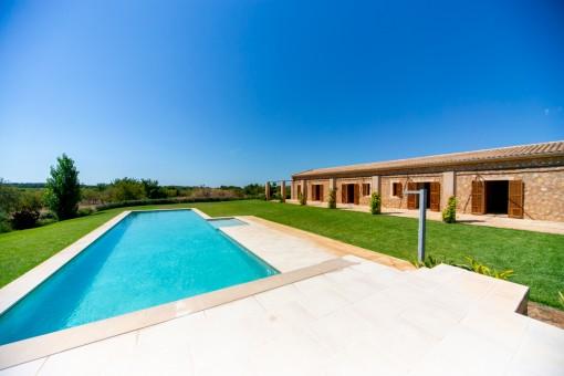 Vista a la piscina soleada y al jardín